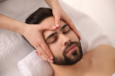 Young man receiving facial massage in beauty salon, above view