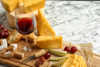 Board with different kinds of delicious cheese, snacks and wine on marble table. Space for text