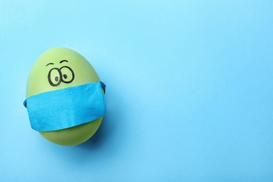 Bright egg in protective mask on light blue background, top view and space for text. Easter holiday during coronavirus quarantine