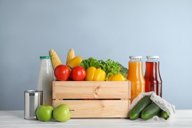 Crate with fresh vegetables and other products on white wooden table against light blue background
