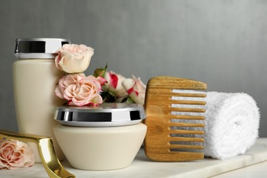 Hair care cosmetic products, beautiful flowers, comb and towel on white table