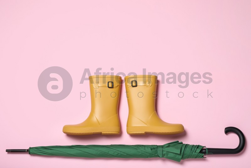 Pair of yellow rubber boots near green umbrella on pink background, flat lay. Space for text