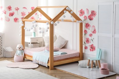 Stylish child room interior with wooden house bed