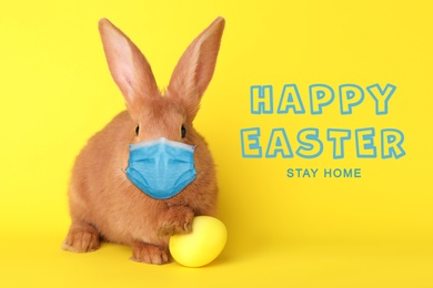 Text Happy Easter Stay Home and cute bunny in protective mask on yellow background. Holiday during Covid-19 pandemic