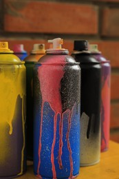 Used cans of spray paints on table near brick wall, closeup. Graffiti supplies