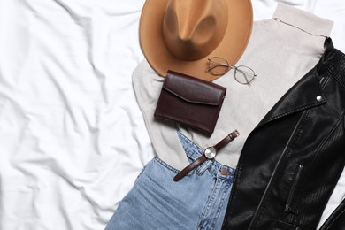 Flat lay composition with stylish hat and autumn clothes on white fabric, space for text