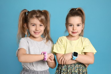 Little girls with smart watches on light blue background