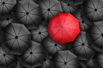 Red umbrella standing out of other ones, top view