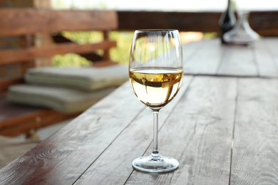 Glass of delicious white wine on wooden table in outdoor cafe, closeup