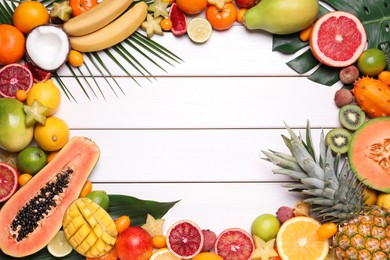 Frame of different exotic fruits on white wooden background, flat lay. Space for text