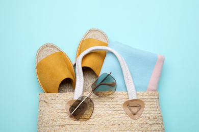 Wicker bag with beach objects on light blue background, flat lay