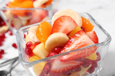 Delicious fresh fruit salad in bowl on table, closeup view