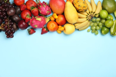 Many different delicious exotic fruits on light blue background, flat lay. Space for text
