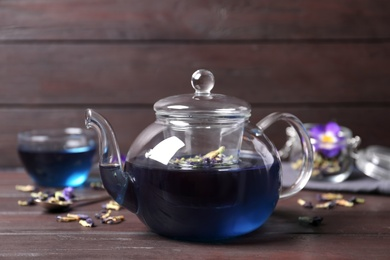 Organic blue Anchan in teapot on wooden table. Herbal tea