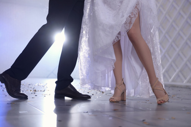 Newlywed couple dancing together in festive hall, closeup of legs