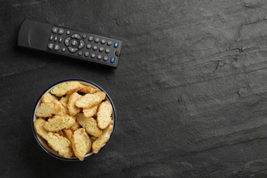 Modern tv remote control and rusks on black table, flat lay. Space for text