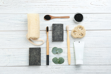 Flat lay composition with bamboo toothbrushes on white wooden table