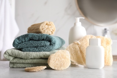 Natural loofah sponges, towels and cosmetic products on table in bathroom