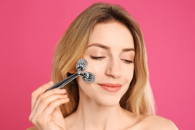 Young woman using metal face roller on pink background