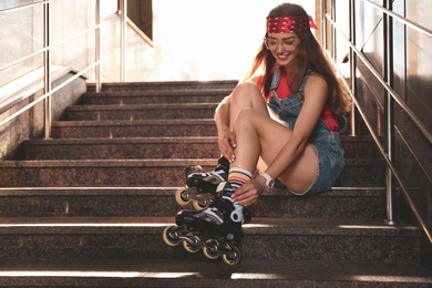 Beautiful young woman putting on roller skates on stairs outdoors, space for text
