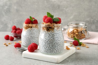 Delicious chia pudding with raspberries and granola on grey table