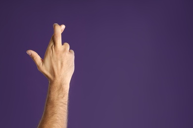 Man with crossed fingers and space for text on purple background, closeup. Superstition concept