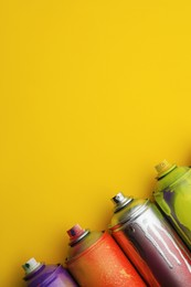 Used cans of spray paints on yellow background, flat lay with space for text. Graffiti supplies