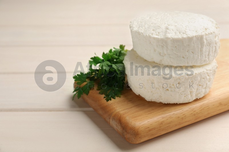 Delicious fresh cottage cheese with parsley on white wooden table, closeup. Space for text