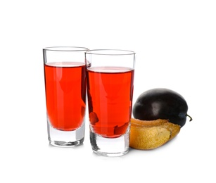 Delicious plum liquor and ripe fruits on white background. Homemade strong alcoholic beverage