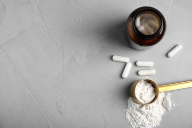 Amino acid pills and powder on grey table, flat lay. Space for text