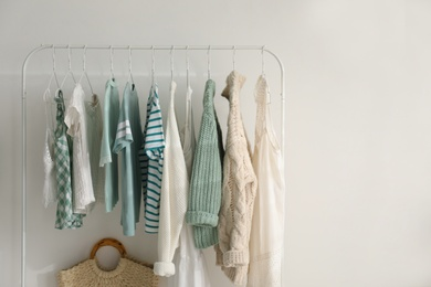 Rack with stylish women's clothes near white wall, space for text. Interior design