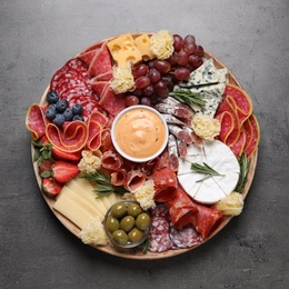 Wooden plate with different delicious snacks on grey table, top view