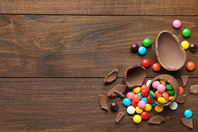 Broken chocolate eggs and colorful candies on wooden table, flat lay. Space for text