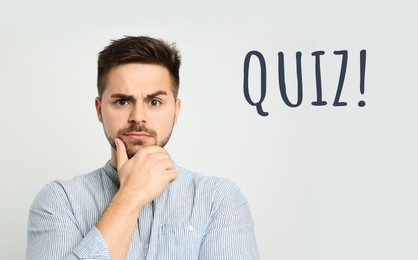 Thoughtful man and word QUIZ on white background
