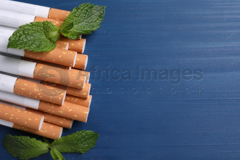 Menthol cigarettes and mint leaves on blue wooden table, flat lay. Space for text