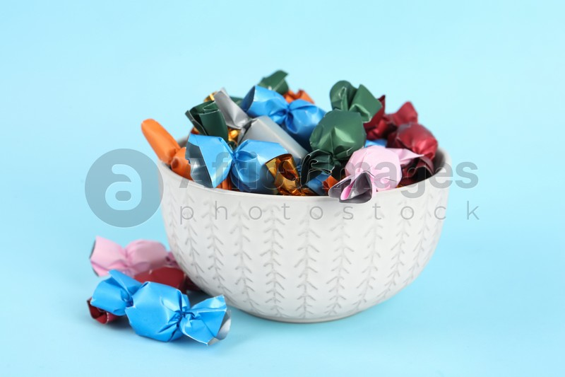 Candies in colorful wrappers on light blue background, closeup