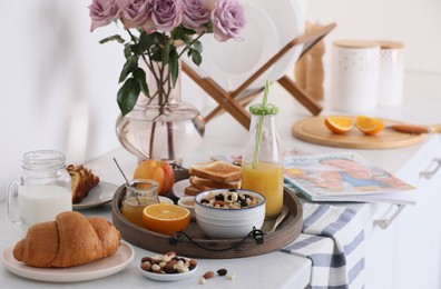Tray with tasty breakfast on white table in morning.  Space for text