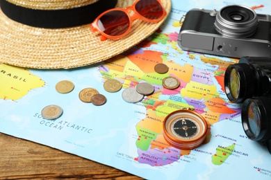 World map and different travel accessories on wooden table, closeup. Planning summer vacation trip