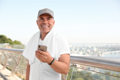 Handsome mature man in sportswear with mobile phone on bridge, space for text. Healthy lifestyle