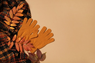Stylish woolen gloves, scarf and dry leaves on beige background, flat lay. Space for text