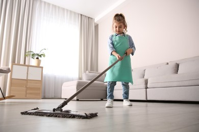 Little girl mopping floor in living room at home
