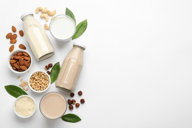 Different vegan milks and ingredients on white background, flat lay. Space for text