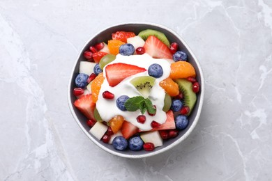 Delicious fruit salad on grey table, top view