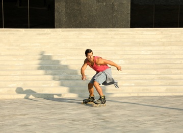 Handsome young man roller skating on city street, space for text