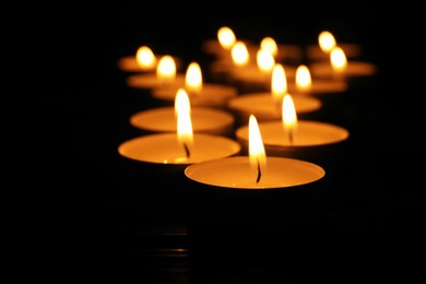 Burning candles on black background, closeup. Memory day