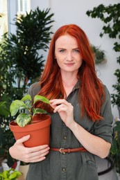 Beautiful woman with green houseplant at home