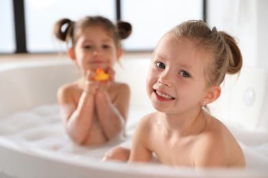 Cute little sisters taking bubble bath together