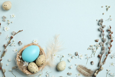Beautiful flat lay composition with flowers and Easter eggs on light background. Space for text