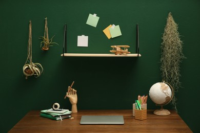Stylish workplace with laptop on wooden desk and different decor near green wall. Interior design