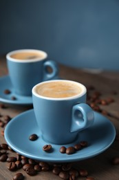 Cups of tasty espresso and scattered coffee beans on wooden table